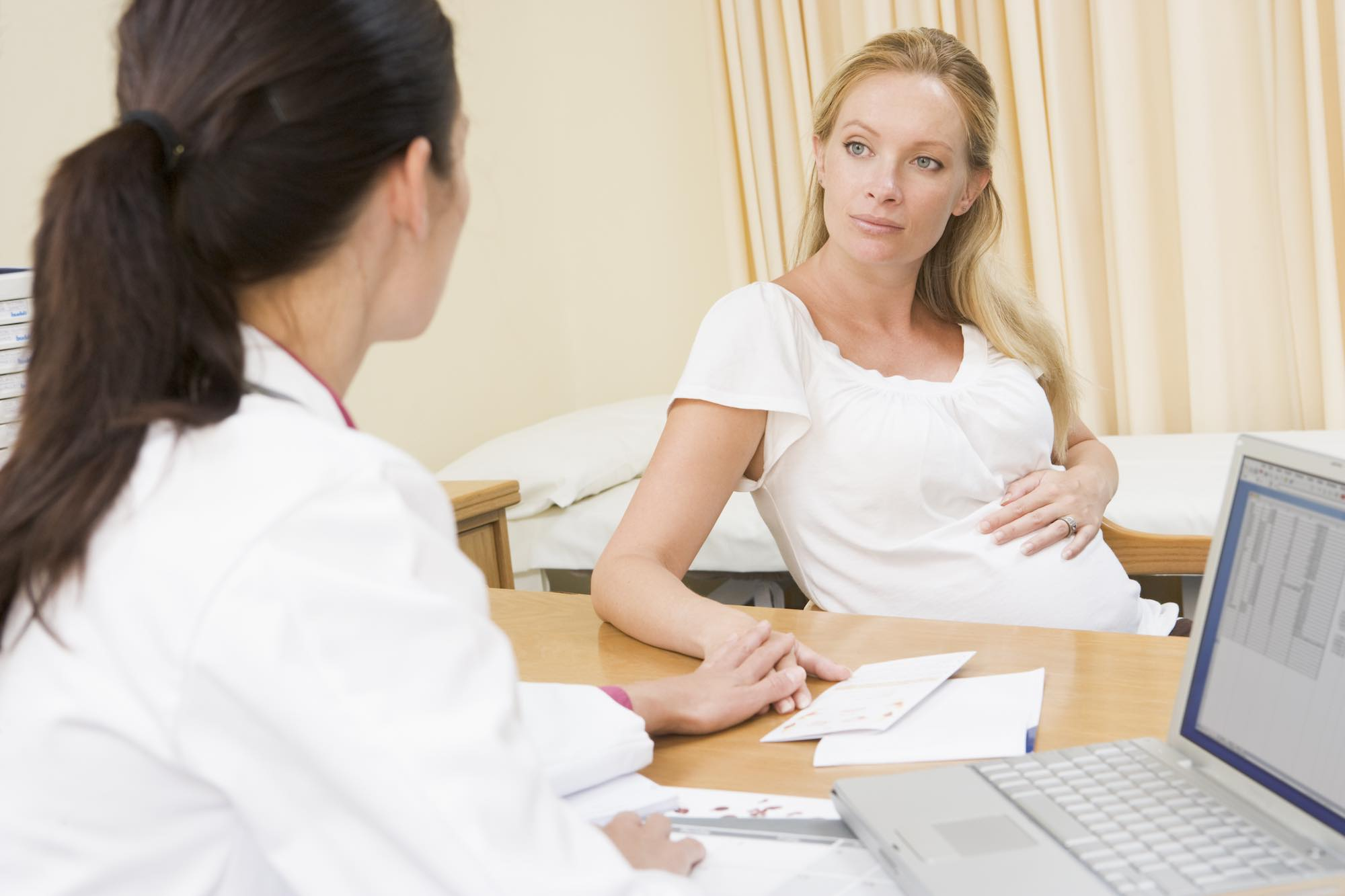 doctor-with-laptop-and-pregnant-woman-in-doctors-office_sizeXL_9749a6