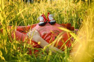 pregnant woman and baby bump sleep position in the grass