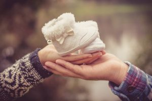 couple hands holding together with white baby girl shoes